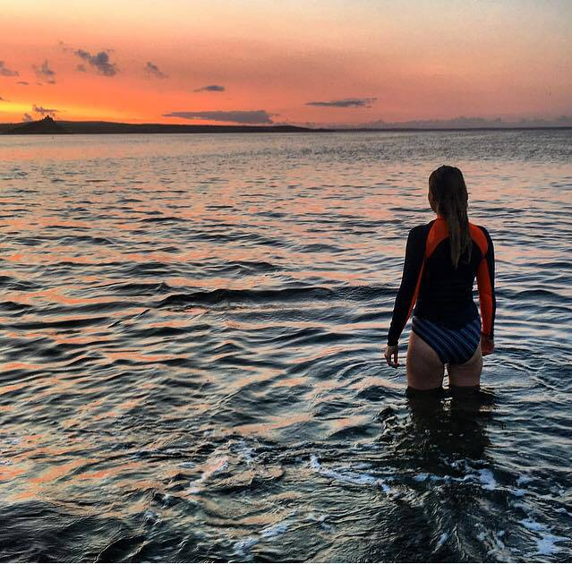 Katie knee-deep in the sea looking at the sunset