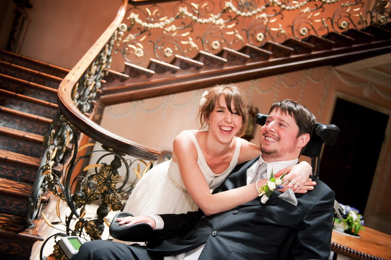 Tom and Ellen on their wedding day by a staircase