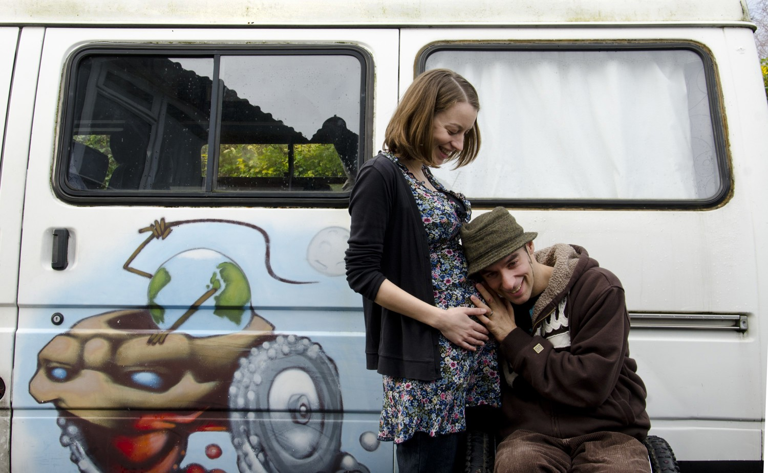 Rob and his pregnant partner next a painted campervan