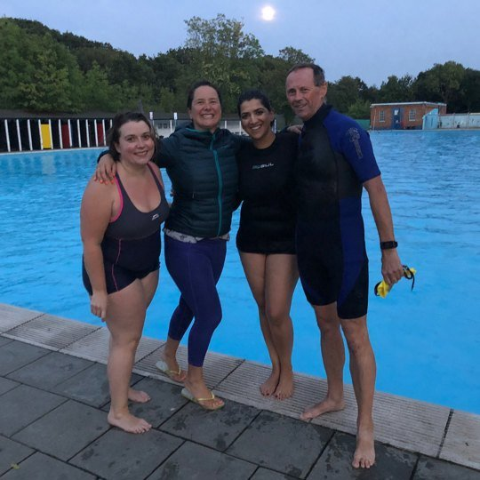 Alice with three others smiling poolside at Tooting Lido