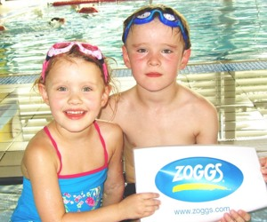 Two young swimmers holding Zoggs sign
