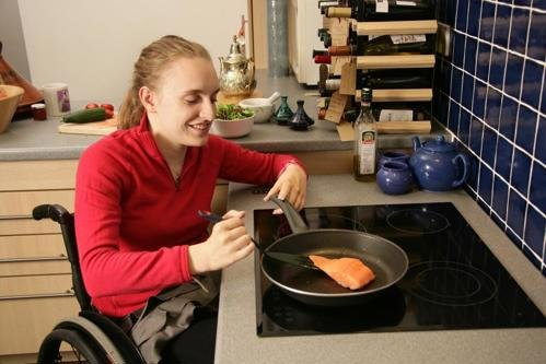 Woman in wheelchair cooking fish