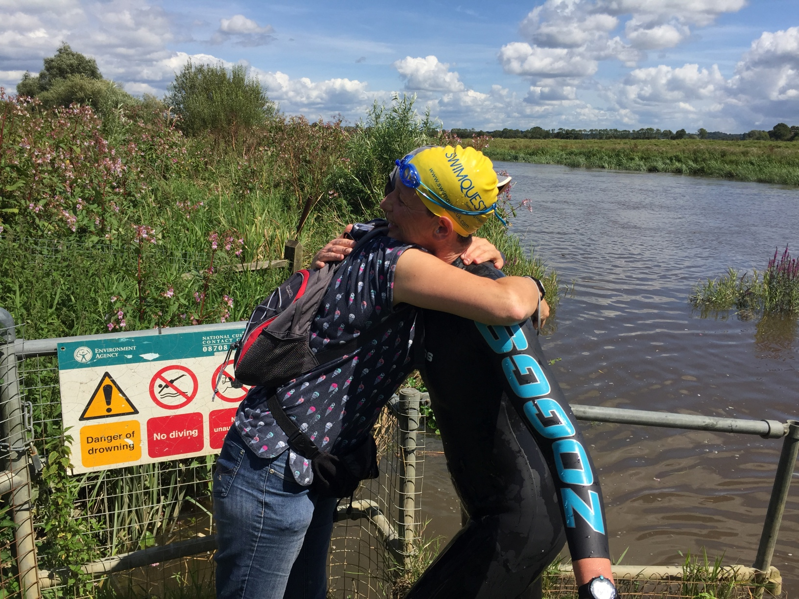 Swimmer embracing a friend after river swim