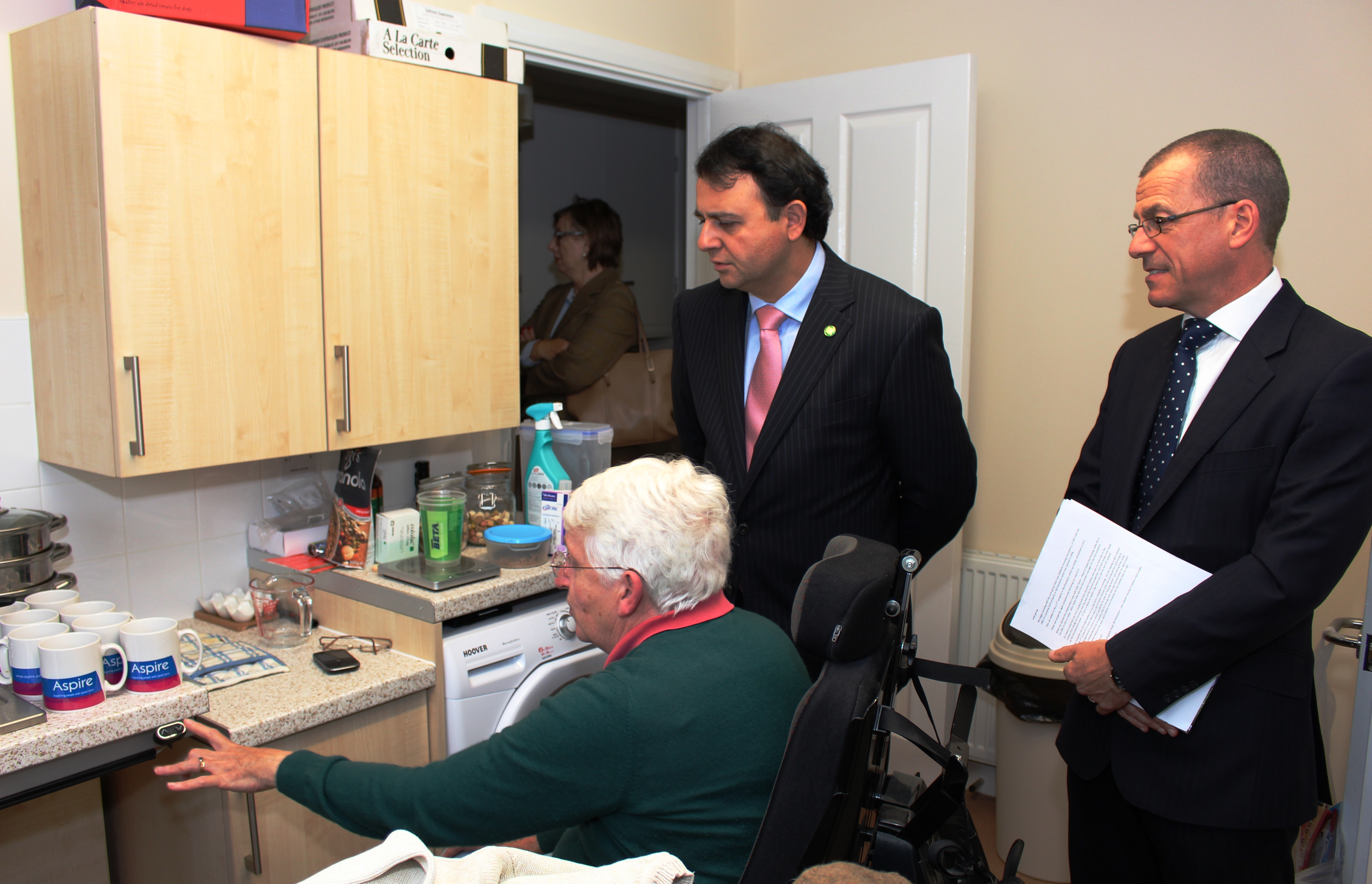 Resident showing Alberto Costa MP the accessible kitchen, with Brian Carlin