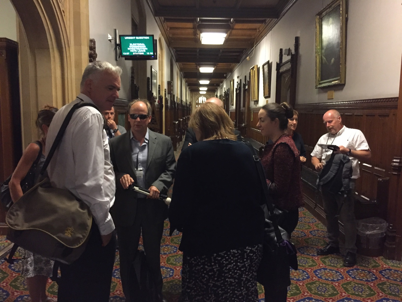 Participants continuing conversations in the corridors after the round table discussion