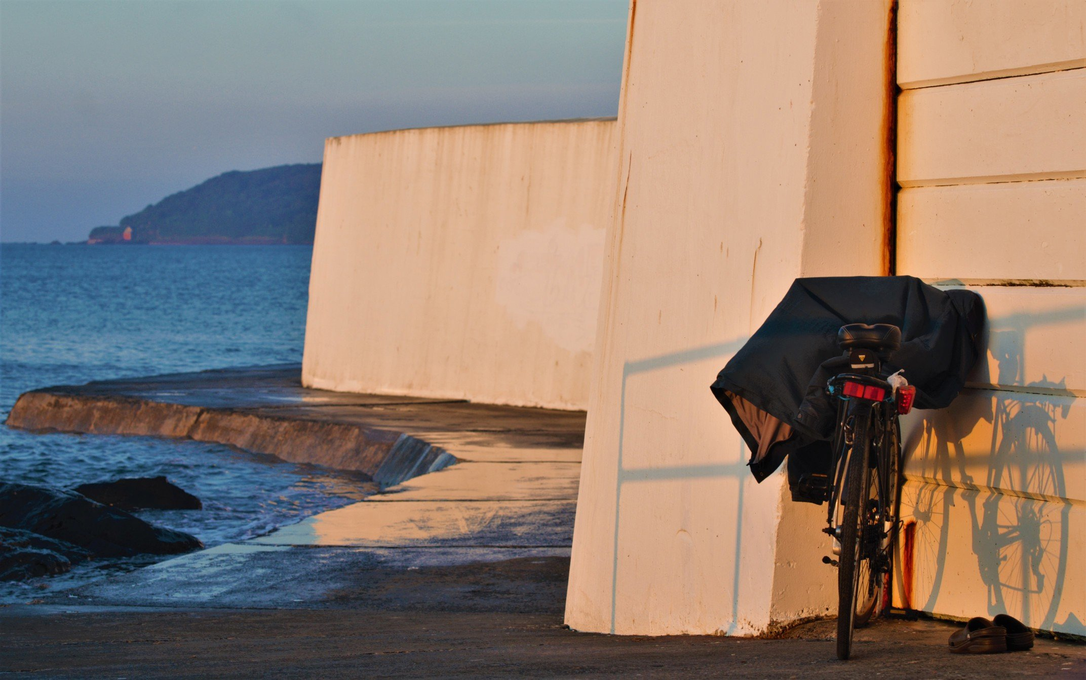 Katies bicycle parked close to the ocean with clothes on the saddle