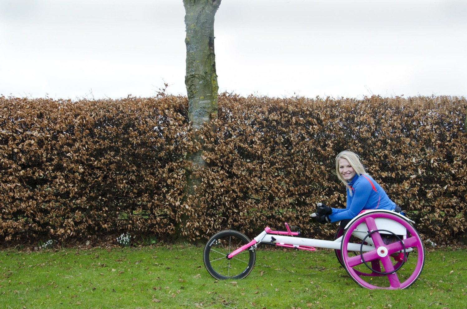 Samantha in her racing wheelchair in front of a hedge