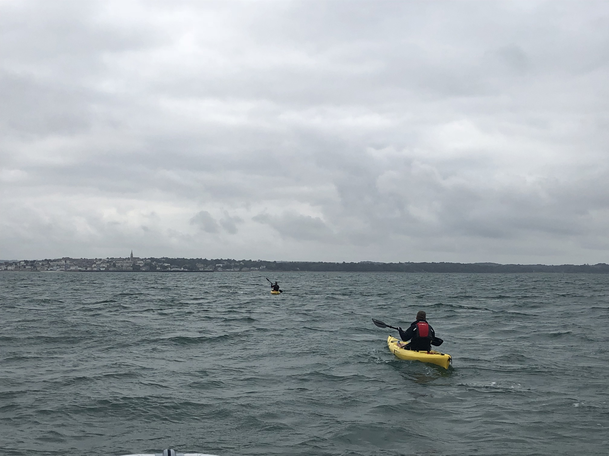 Swimmer with their kayaker behind and the Isle of Wight in the distance