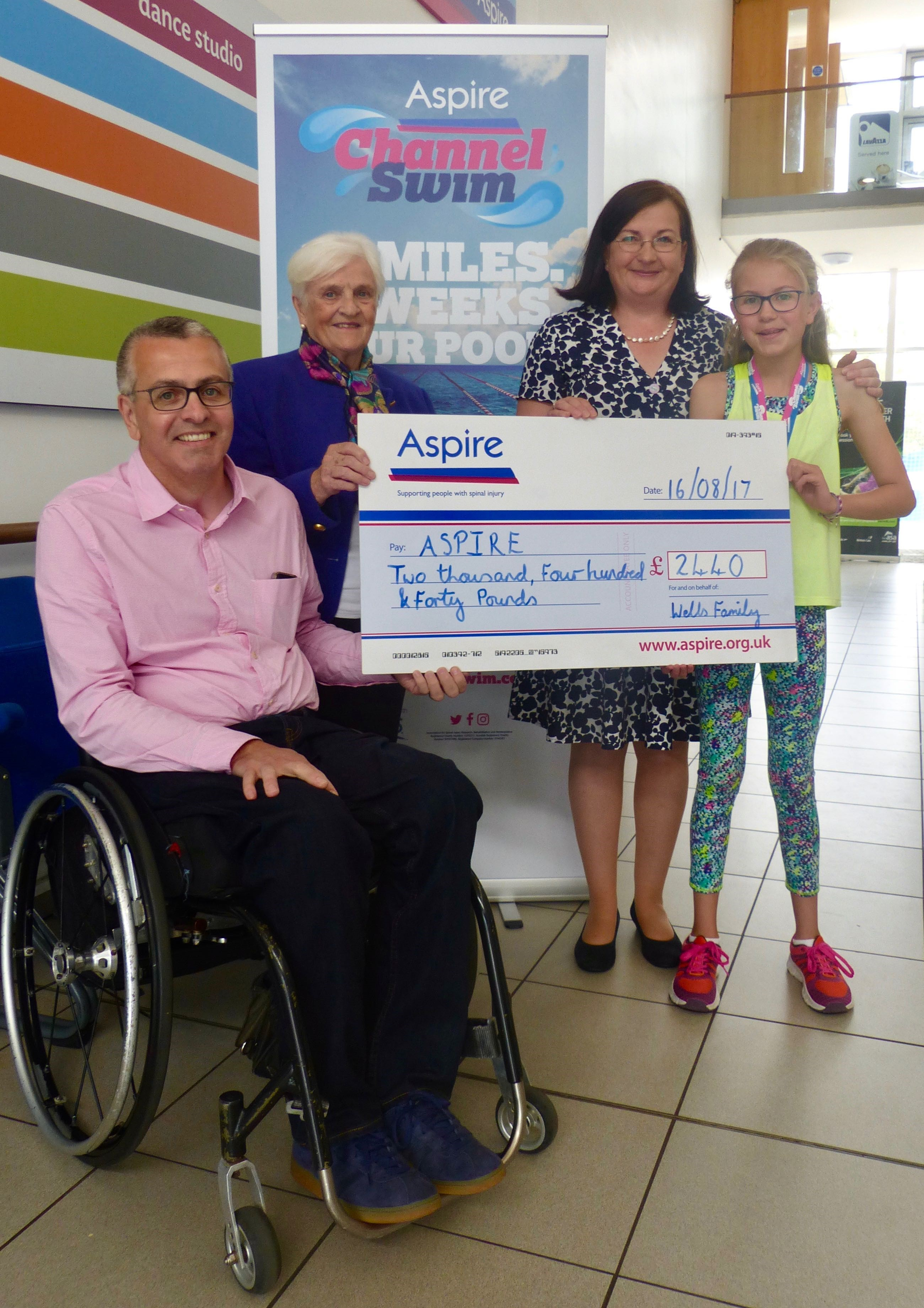 Peter, Valerie, Mary and Lily Wells present large cheque