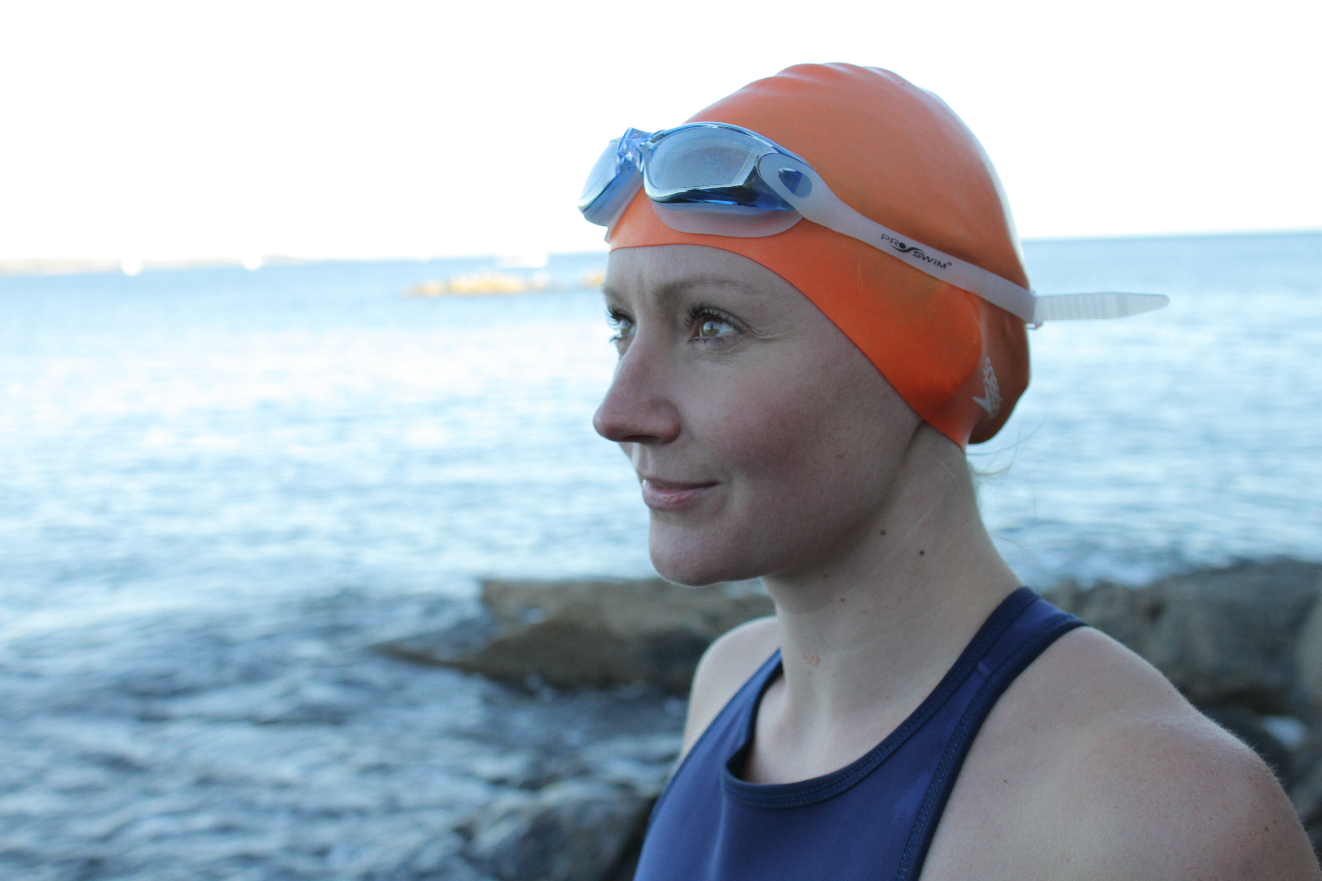 Katie in swimming hat and goggles with the sea as a background
