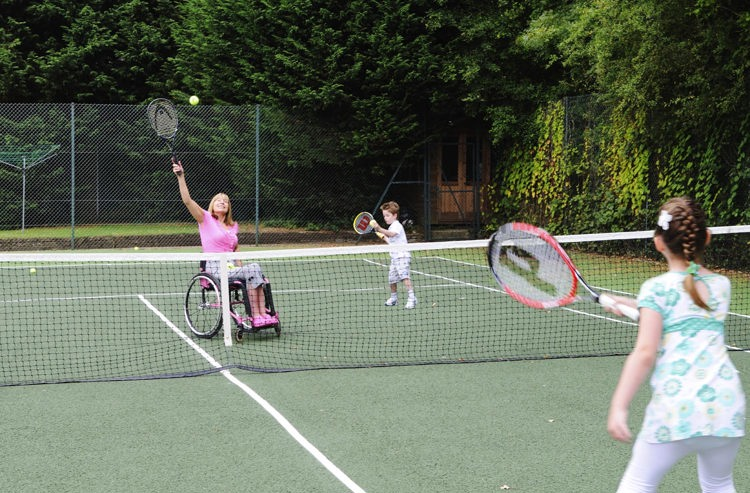 Lady in wheelchair playing tennis with her children