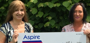 Skydiver Jane and Aspires Hannah holding cheque