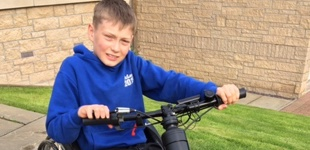 Callum using his new hand bike attachment