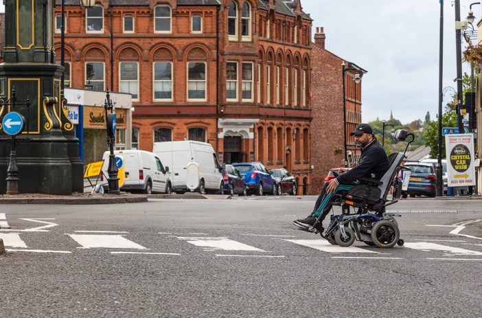 Man in wheelchair crossing the road on a zebra crossing