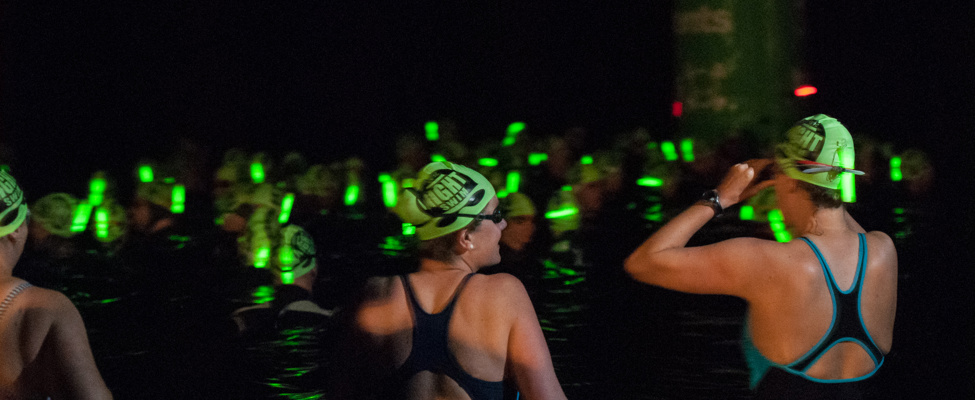 Swimmers getting into the water at night