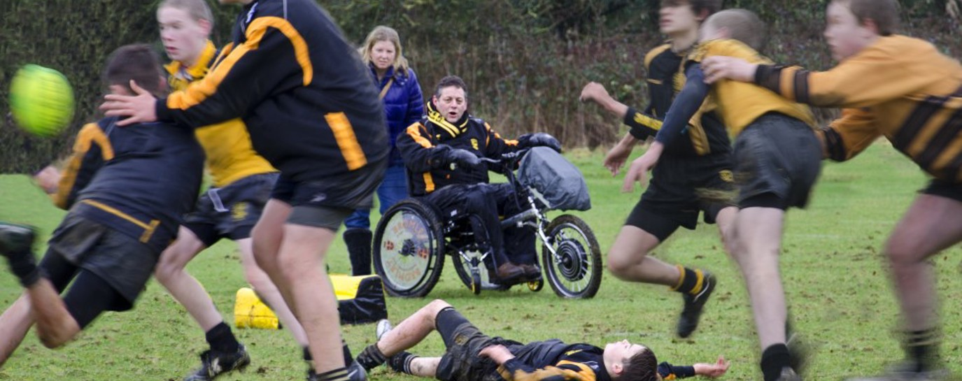 Tim in his wheelchair watching his son play junior rugby