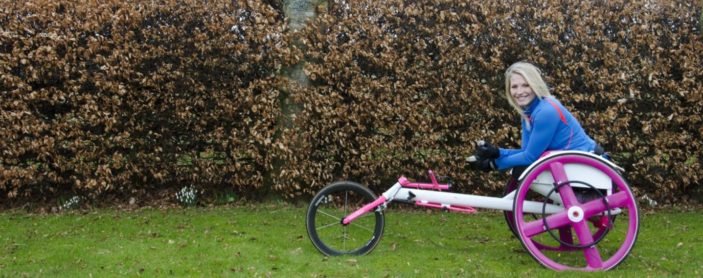 Samantha in her racing wheelchair by a hedge