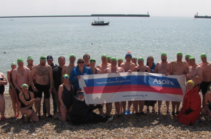 Swimmers on beach holding Aspire banner