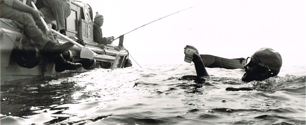 A black and white image of Kevin treading water next to a support boat