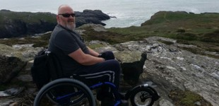 Phil by the sea in his wheelchair