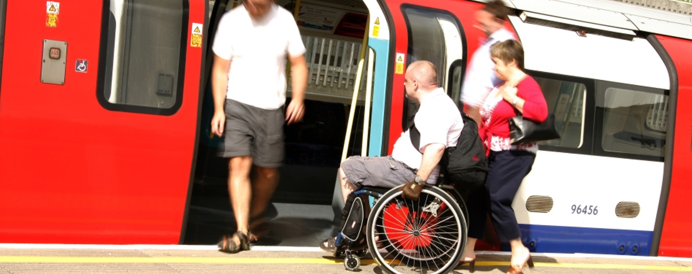Man in wheelchair getting on a tube train