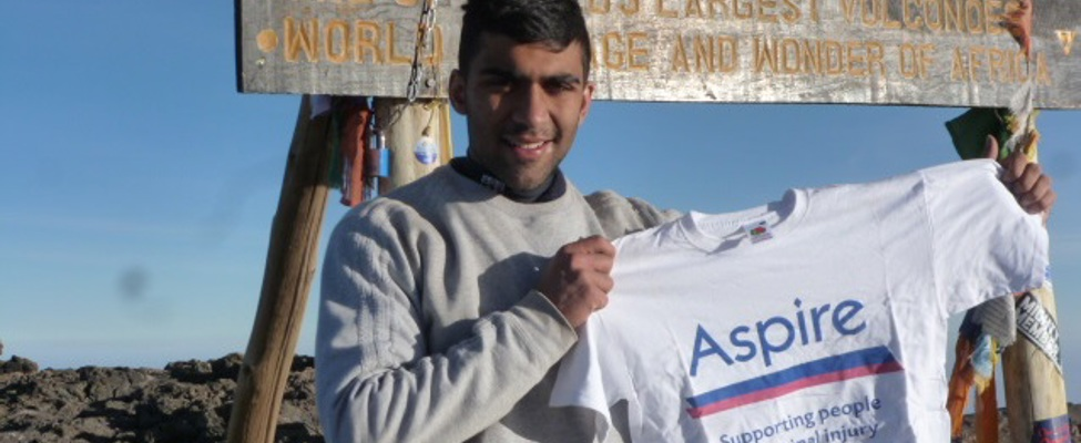 Akshay Pabary holding Aspire t-shirt at the summit of Mount Kilimanjaro