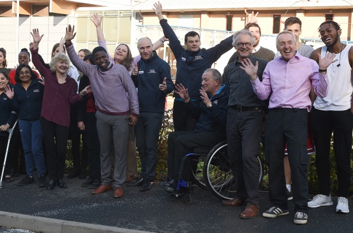 A collection of Aspire staff waving and cheering outside the charity
