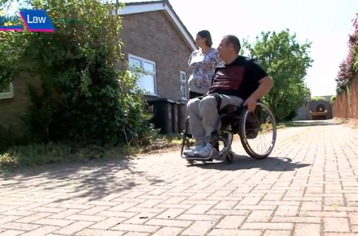 Wheelchair user and wife outside house