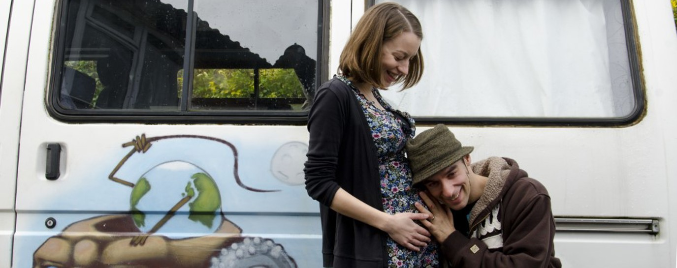 Rob and his pregnant partner next to their painted campervan