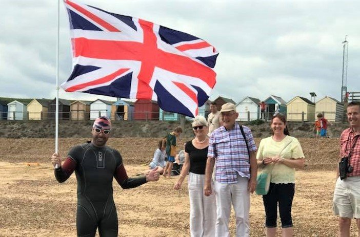 Richard on the beach with the British flag after his swim