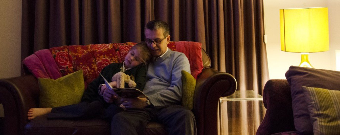 Thomas sitting on the sofa reading to his daughter