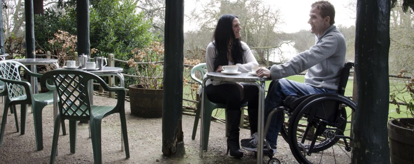 James, in his wheelchair, having tea outside with his girlfriend
