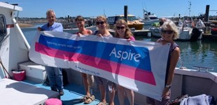 Swimmers on a boat holding Aspire banner