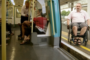 Man in wheelchair by tube train