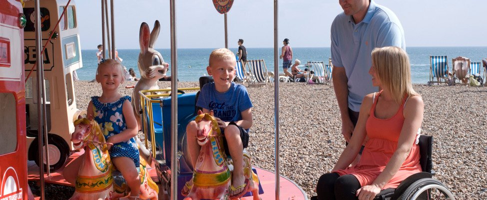 Lightweight wheelchair user and family at Brighton beach amusements