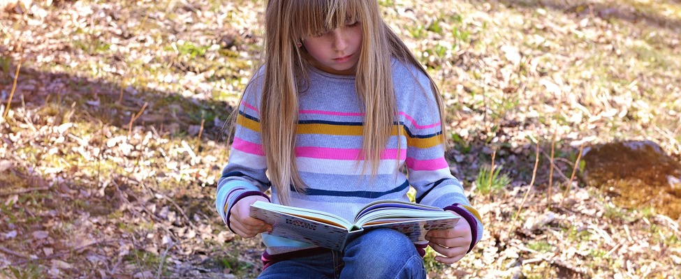 Child sitting reading a book
