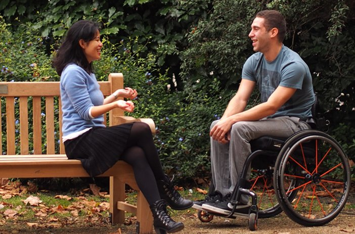Wheelchair user and friend in park