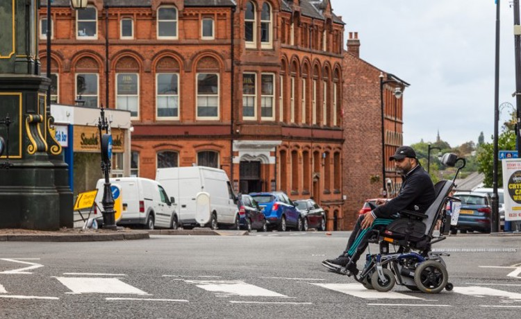 Disabled man in wheelchair on zebra crossing